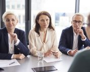 Office workers in a meeting | Featured image for performance evaluation process blog.
