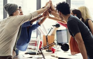 Team high fives in office | Featured image for culture vs strategy blog.