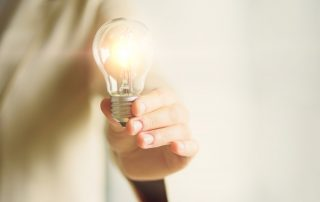 Person holding lightbulb | Featured image for HR Challenges in startups