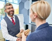 Man shakes hands with woman | Featured image for rewards and recognition in the workplace.