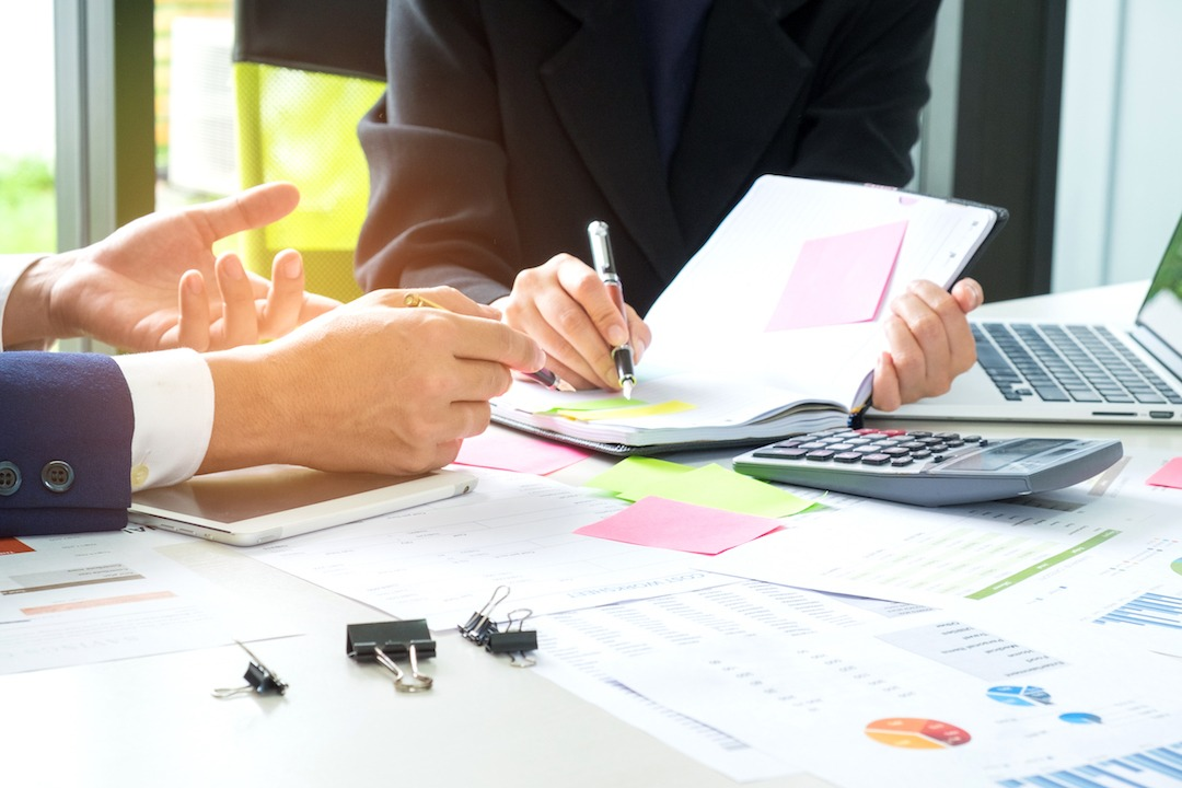 People working on different documents | Featured image for Quality Management Systems blog