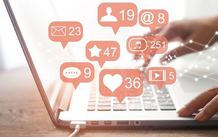 Laptop with social media icons | Featured image for social media use in the workplace